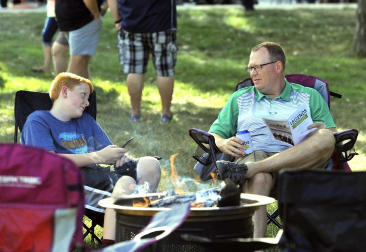 -Messenger photo by Hans Madsen  Caleb Schaeffer, 12, at left, of Fort Dodge, enjoys some father son time with his dad, Chad Schaeffer, as they relax in front of an open fire at the Friendship Haven Legends Tailgate fundraiser Friday evening. Proceeds from the event benefit Friendship Haven's Good Samaritan Fund.