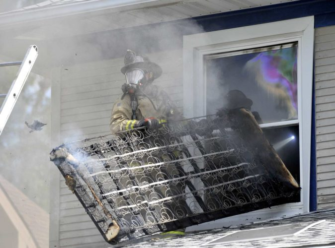 -Messenger photo by Hans Madsen  Fort Dodge firefighter Pat Greve helps remove a burned up box spring from an upstairs bedroom Friday afternoon at 1607 Fourth Ave. S. as crews work to put out a fire in the home.