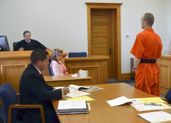 -Messenger photo by Joe Sutter  Timothy Wood, right, speaks to Chief Judge Kurt Wilke, of the 2nd Judicial District, during a guilty plea hearing in Webster County District Court Monday. Wood pleaded guilty to second-degree arson. First Assistant Webster County Attorney Ryan Baldridge takes notes at left.