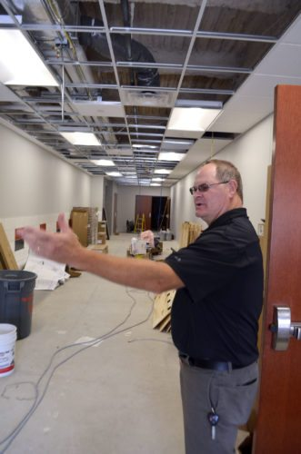 -Messenger photos by Joe Sutter   Travis Filloon explains the layout of the lobby for Fort Dodge Senior High's new auxiliary gym, which will have a family restroom and men's and women's rooms, and can be opened without opening the school for events. Filloon said the structure should be ready by the time school starts.