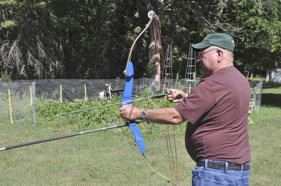 -AP photo  4-H archery instructor Dave Anderson holds a bow recently. Anderson is one of several area 4-H'ers to be inducted into the 4-H Hall of Fame on Aug. 20.