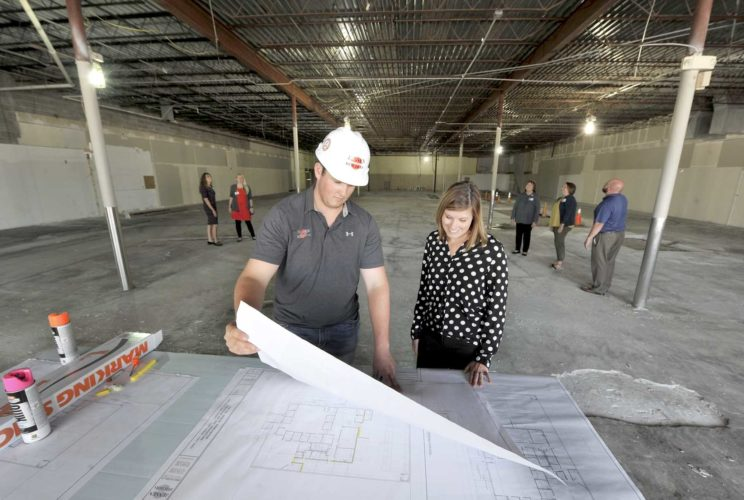 -Messenger photo by Hans Madsen  UnityPoint at Home executive director Jennifer Crimmins, at right, along with Jensen Builders project manager Taylor Pedersen, look over plans for the new retail store in the former HyVee Drugstore building. Homecare clinical manager Julie Samuelson, at left, Homecare clinical supervisor Jen Kirchhoff, warehouse supervisor Doris McBurney, regional store manager Angie Tracy and store unit supervisor Mike Hanrahn, at right, look over the cite behind them.