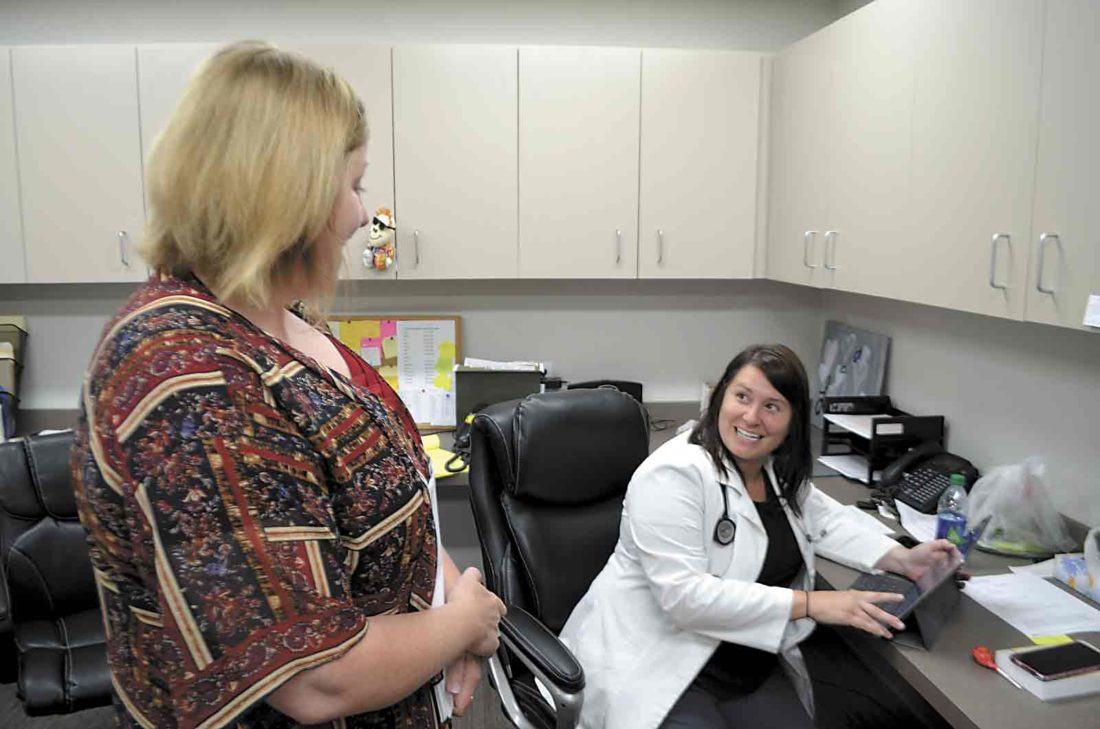 "-Messenger photo  by Joe Sutter  Community Health  Center COO Colleen Koester, left, talks with nurse practitioner Lisa Chase in one of the new administrative ""pods"", which let staff all work together in the same room. Chase said the patients appreciate the new building."