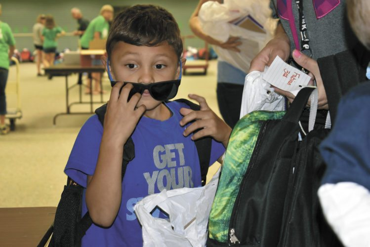 -Messenger photo by Chad Thompson  Royce Mora, 6, of Duncombe, pulls down his new shades at Crossroads Mall during the 15th annual Back to School Bash Tuesday night.