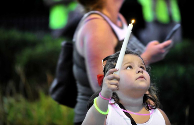 -Messenger photo by Hans Madsen  Maria Gomez, 6, of Fort Dodge, holds a candle Thursday evening as she watches balloons rise into the sky during a candlelight vigil for her mom, Jessica Gomez, 26, of Fort Dodge. Gomez went missing earlier this month, her body was found near Clare on Aug. 12.
