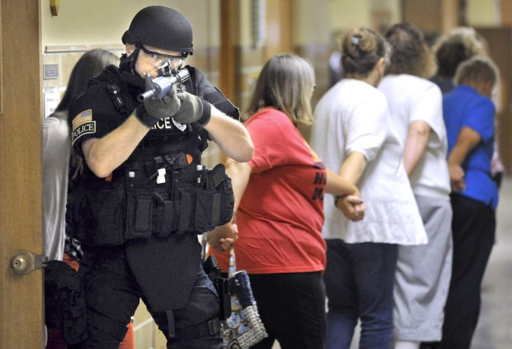 -Messenger photo by Hans Madsen  Fort Dodge Police officer Bryan Slama covers the hallway as a group of school staff leave a classroom at St. Paul Lutheran School during an active shooter drill.