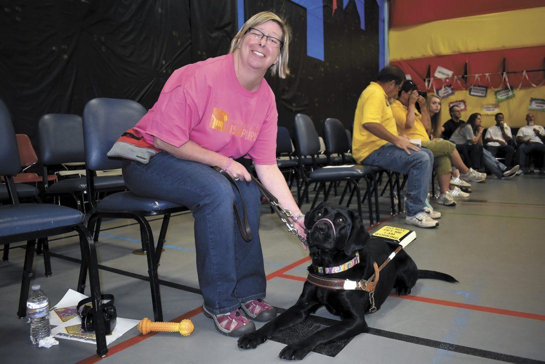 -Messenger photo by Chad Thompson  Dawn Rudolph, of Hamilton, Michigan, sits with her leader dog, Lady, during Puppy Days at the Fort Dodge Correctional Facility Sunday afternoon.