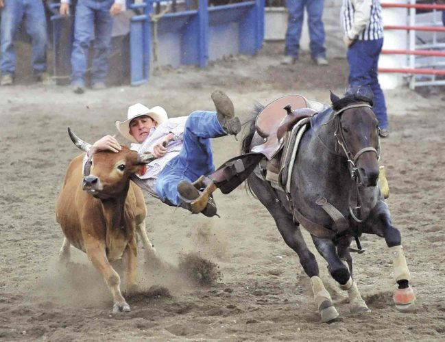 -Messenger file photo  Jon Ragatz, of Beetown, Wisconsin, jumps off his horse during his run in the calf wrestling event at the Dayton Rodeo in 2016.