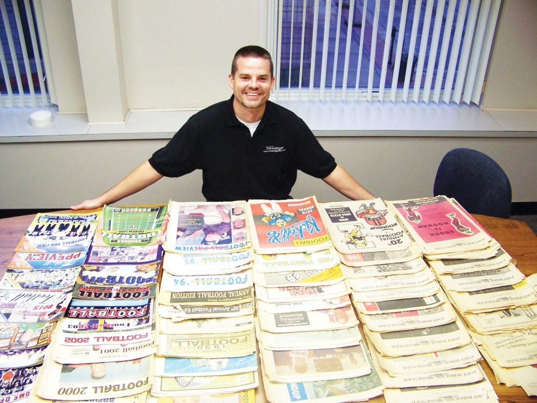 Messenger photo  Sports Editor Eric Pratt displays the 59 different Messenger football previews.