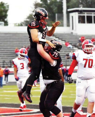 —Messenger photo by Britt Kudla  DRAKE MILLER gets picked up by Fort Dodge lineman Logan Finowski after a touchdown on Friday inside Dodger Stadium. For more photos, please visit CU at messengernews.net