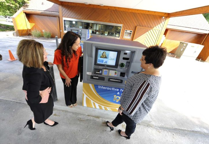 -Messenger photo by Hans Madsen  First Amerian Bank President Susan Ahlers Leman, at left, along with finance services representative Bernardette Schultz and Natalie Newell, vice-president of retail banking, look over the newly installed Interactive Teller Machine at their east Fort Dodge location. The device lets the bank's customers complete their ITM transaction with a live representative on the video screen.