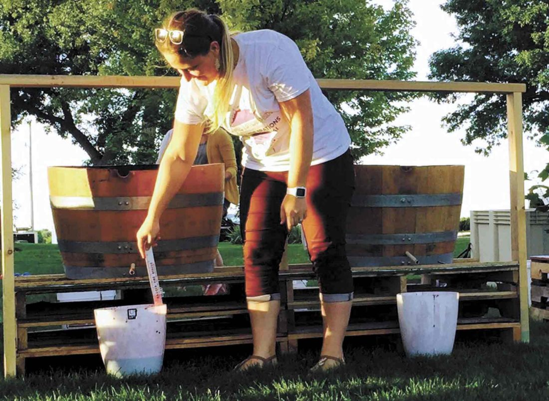 "-Submitted photo Soldier Creek Winery employee Mary Alves measures how much juice the stompers got in the 2016 Good ""Vine""brations Harvest Festival."