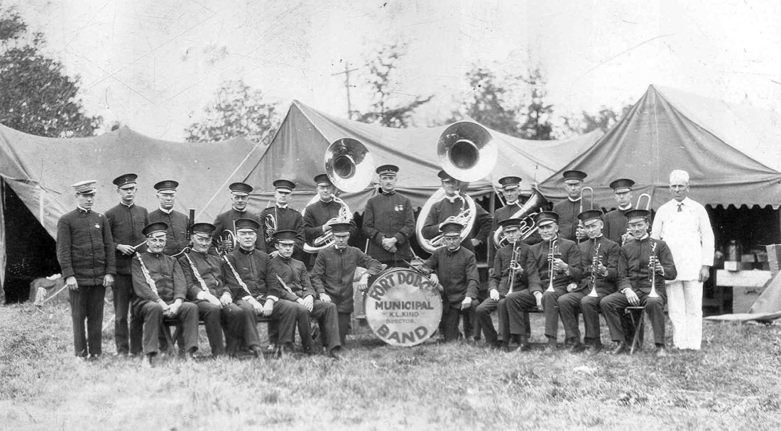 -Submitted photo The Fort Dodge Municipal Band is pictured in 1928. The band played at the fair in Spencer that year and is pictured in front of the band's tent camp with the cook. Conductor Karl L. King is in the center of the photo, between the two sousaphone players.