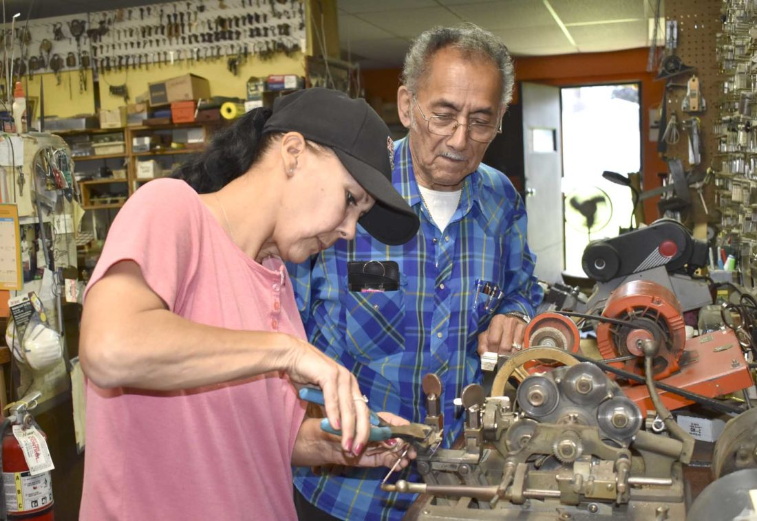 -Messenger photo by Chad Thompson  Monica Sortedahl, of Fort Dodge, works on making a copy of a key at Rosalez Lock and Key Service. Her father, Dave Rosalez, also of Fort Dodge, looks on.
