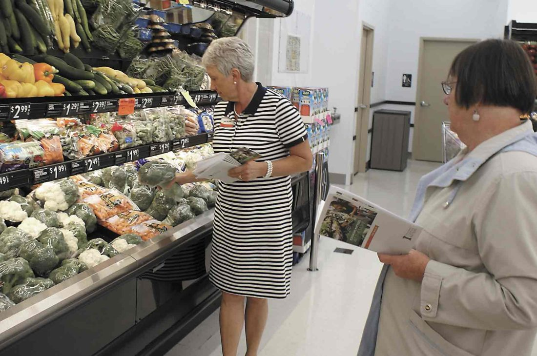 -Messenger photo by Dawn Bliss Holly Van Heel, left, health and nutrition specialist with the Humboldt County Iowa State University Extension Office, discusses what to consider when buying fresh vegetables to get the most for your money while Darlene Broughton, of Humboldt, listens to the tips.