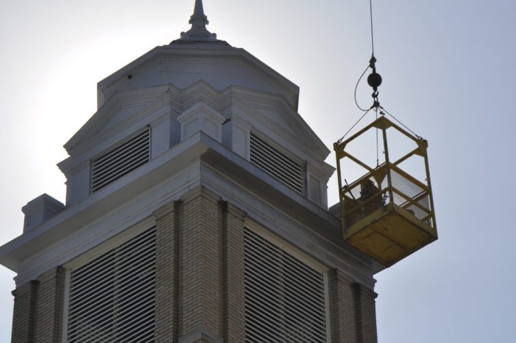 -Messentger photo by Joe Sutter  Ferguson Painting, of Farnhamville, puts a fresh coat of white paint on the top of the First United Methodist Church's 110-foot tall bell tower Friday.