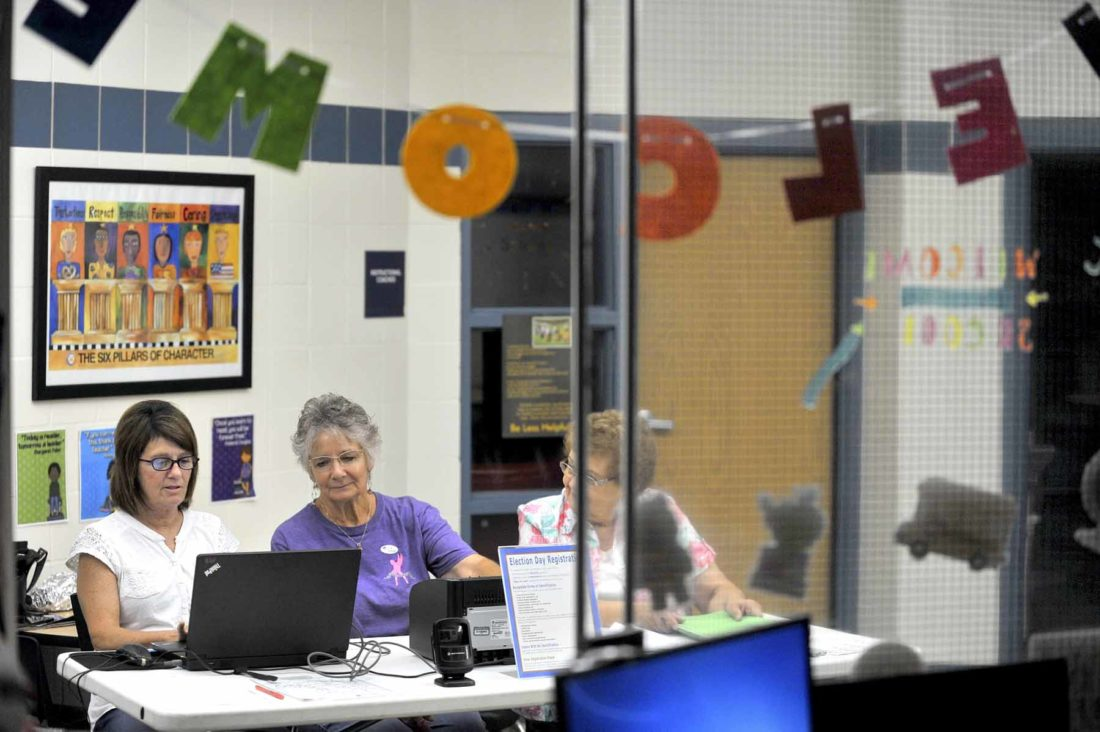 -Messenger photo by Hans Madsen  Framed by the office window, precinct election officials Kathy Porrez, at left, Deb Schuh and Norma Hughett, right, wait for Precinct 8 voters Tuesday afternoon at Butler Elementary School. Turnout in the election was light; as of 6:10 p.m. 11 voters had cast ballots there. That included the three cast by each of them. Hughett said the first voter made it to the polls, which opened at 7 a.m., at 9:55 a.m.