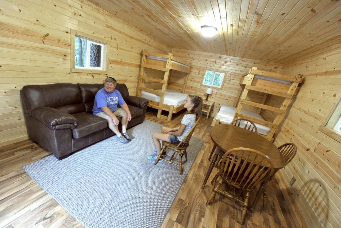 -Messenger photo by Hans Madsen  Steve Johanson, of Badger, and his granddaughter, Kylie Crimmins, 13, of Fort Dodge, check out the interior of the cabin at the Webster County Conservation Camp WaNoKi site Tuesday afternoon during an open house. The ceiling lights are solar powered.