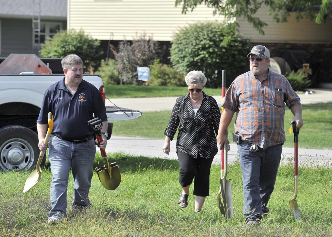 -Messenger photo by Hans Madsen  Badger Mayor Chris Wendell, at left, City Clerk Nadine Odor and city worker Dave London carry the city's full complement of gold shovels Tuesday morning during a groundbreaking for the new Badger Ridge housing development in Badger.