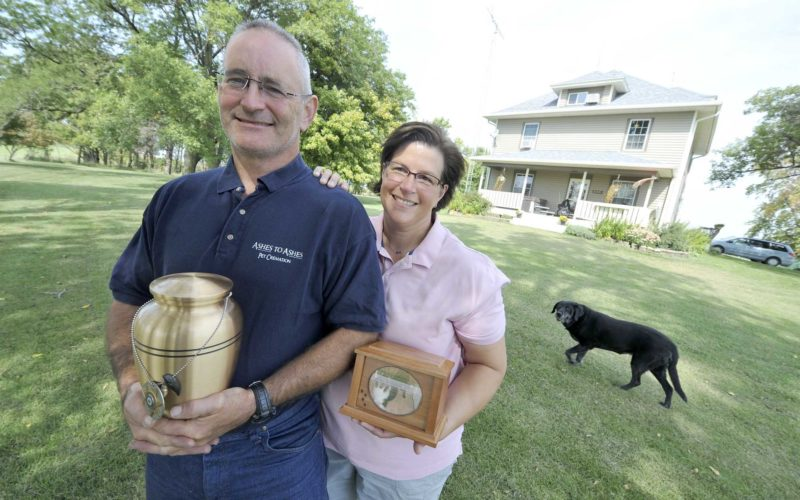 -Messenger photo by Hans Madsen  Scott and Aimee Devereaux, owners of Ashes to Ashes Pet Cremation pose at their business near Pomeroy as Bailey walks by on the lawn. They began the business when Scott, then a Pocahontas County Deputy, had his canine partner Bear killed and they were unable to locate a proper cremation service. Scott is holding Bear's ashes, badge and a bronzed tooth.