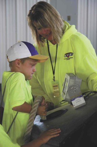-Messenger photo by Karen Schwaller  Shelly Mortenson of Cooperative Farmer's Elevator, Ocheyedan, led a station that taught children about the dangers of flowing grain. Here, she leads a hands-on effort to show the children how difficult it is to pull someone who has become entrapped in a grain bin.