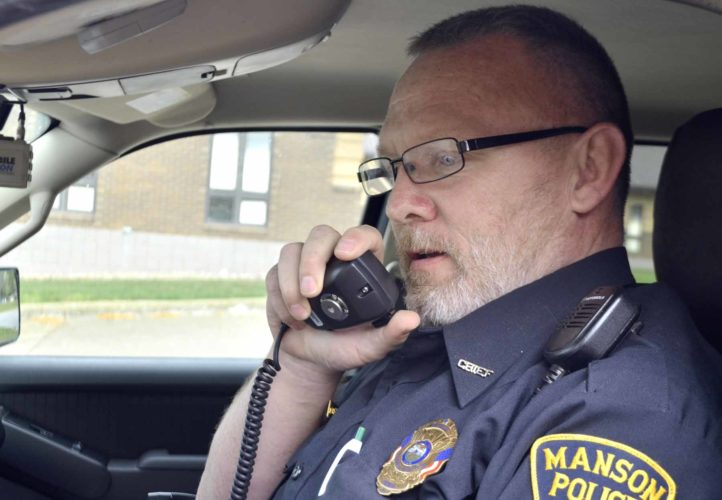 -Messenger photo by Peter Kaspari  Manson Police Chief Gerald Frick makes a call on his radio in his patrol vehicle.