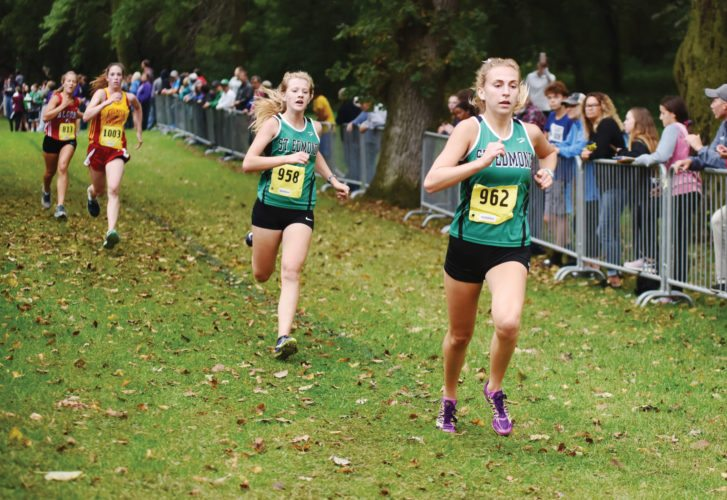 Messenger photo by Britt Kudla  St. Edmond teammates Audrey Kolacia (left) and Riley Mayer run in the Humboldt Invitational on Monday. For more photos, please visit CU.messengernews.net