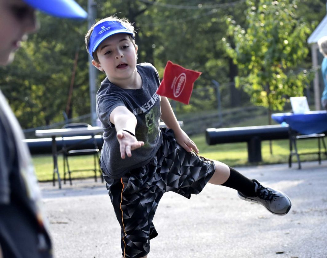 -Messenger photo by Chad Thompson  Greyson Chance, 8, of Fort Dodge, lets one fly during a mini bags game against his brother Paxton Chance, 5, Tuesday night at Oleson Park.
