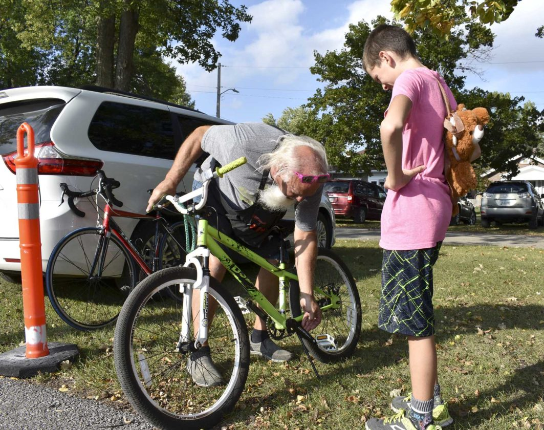 -Messenger photo by Chad ThompsonCaden Waychoff, 12, of Fort Dodge, right, gets some help with his bike from Gene Walker, of The Bike Shop during the Prairie Rivers Trail Expansion Oleson Park Celebration Tuesday night.