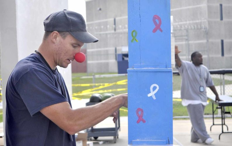 -Messenger photo by Peter Kaspari  Daniel Anthony, an inmate at the Fort Dodge Correctional Facility, wears a clown nose as he sets up a game at the Insiders' Relay for Life.