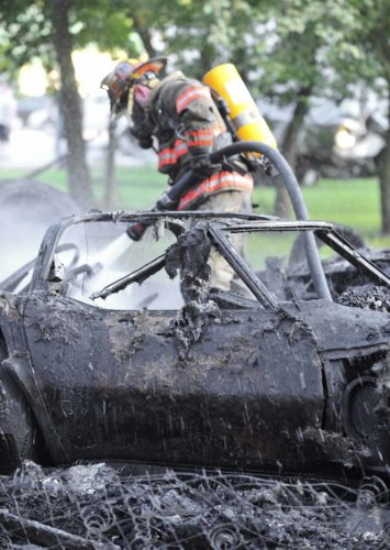 -Messenger photo by Hans Madsen  With the smoldering remains of a vintage Corvette in the foreground Humboldt firefighter Matt Ubben sprays water on a garage fire late Thursday afternoon in Dakota City. Several collectable vehicles stored in the garage were destroyed.