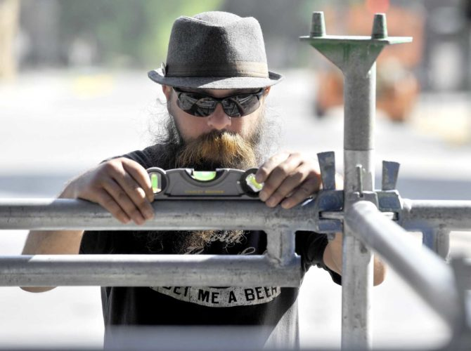 -Messenger photo by Hans Madsen  Stagehand Ben Vrieze, of Fort Dodge, uses a level to check a section of the stage as he works on setting up for tonight's Downtown Country Jam.