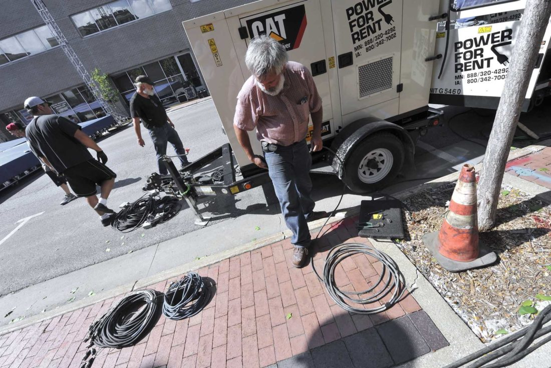 -Messenger photo by Hans Madsen  City of Fort Dodge electrician Steve Mattke works on helping to get the generator wired up Friday afternoon during setup for tonight's Downtown Country Jam.