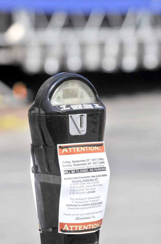-Messenger photo by Hans Madsen  One of the parking meters on Central Avenue, with the stage behind it, displays a notice that the area won't be available for parking due to the Downtown Country Jam. Organizer Jim Reed said there's plenty of parking available downtown for concert goers.