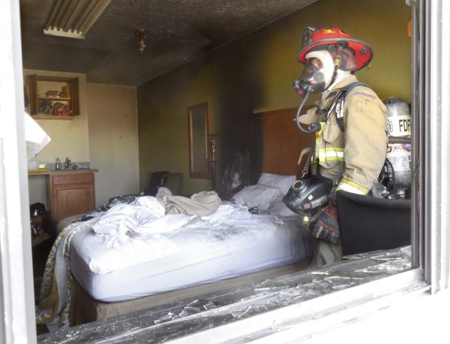 Messenger photo by Bill Shea Fort Dodge Fire Department Capt. Steve Teske examines a fire-damaged room at the Days Inn, 3040 Fifth Ave. S., Saturday morning. The fire damaged a two-room suite and filled the building with smoke. No one was injured.