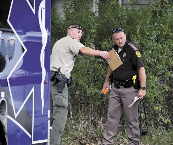 -Messenger photo by Chad Thompson  Justin Wood, Webster County sheriff's deputy, left, and Trooper Neil Morenz, of the Iowa State Patrol, communicate following a fatal motorcycle crash along Samson Avenue, southeast of Lehigh Sunday afternoon.