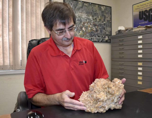 -Messenger photo by Chad Thompson  Matt Benzie, of Fort Dodge, looks over a Bristol mine gypsum crystal in his office at USG recently. The crystal is one of about 400 rock samples Benzie has in his collection.
