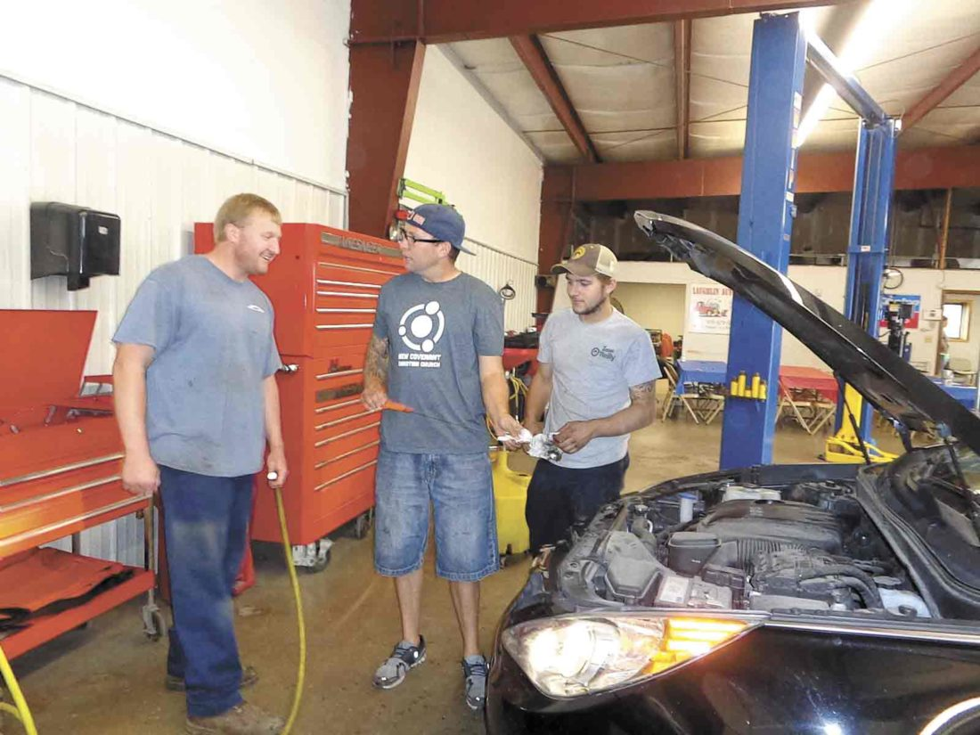 -Submitted photo Ed Plansky and Doug Rushton, a children's pastor at New Covenant Church, work together on an oil change during this event in 2016.