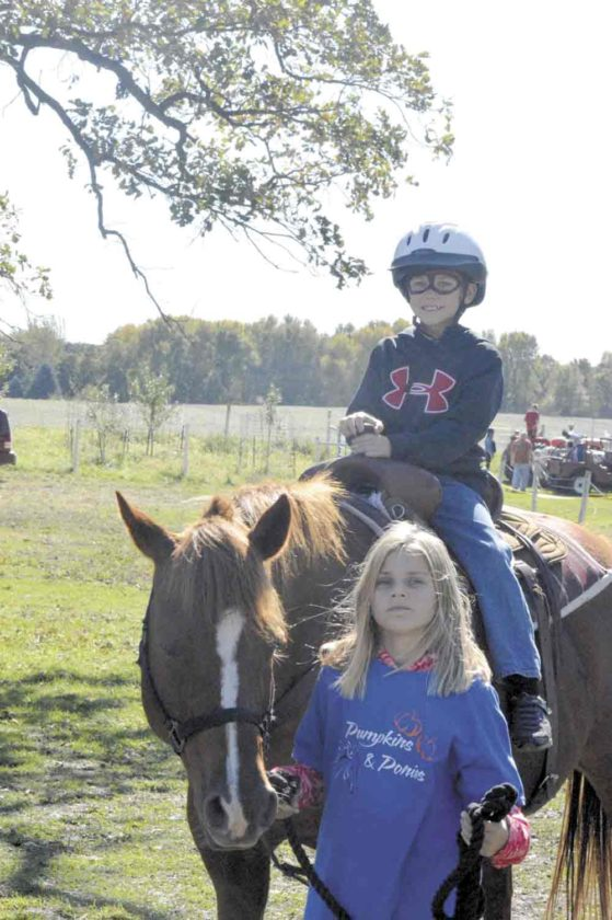 Bella Opheim leads a pony carrying a young rider during a past Pumpkins and Ponies event at SpringVale Farm in Humboldt County.