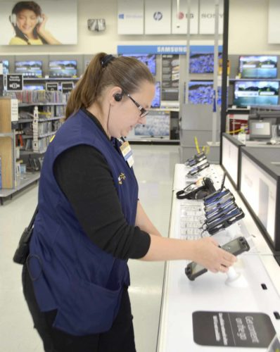 -Messenger photo by Peter Kaspari  Melissa Regan, a Walmart sales associate, works with a tablet in the store's recently-remodeled electronics department in the Fort Dodge store.