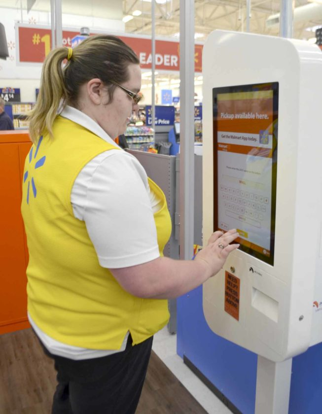 -Messenger photo by Peter Kaspari  Samantha Mallinger, a Scan and Go host at Walmart, demonstrates how the store's newly-relocated pickup center works. Store Manager Brad Henderson said the pick up center is now located at the front of the store instead of the back, and all the items are stored in lockers for the customer's convenience.