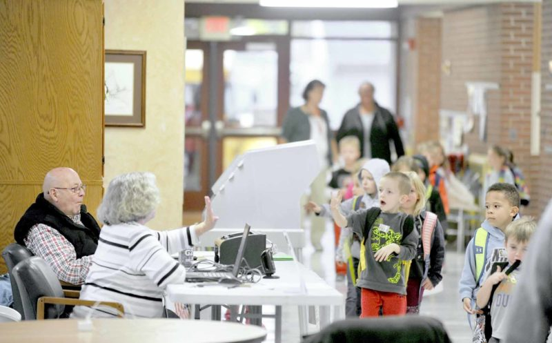 -Messenger photo by Hans Madsen  Precinct election official Vickie Kesling waves to a group of students leaving Cooper Elementary School for the day Tuesday afternoon as fellow official Bruce McCullough watches at left. Cooper is the polling place for Precinct 11.