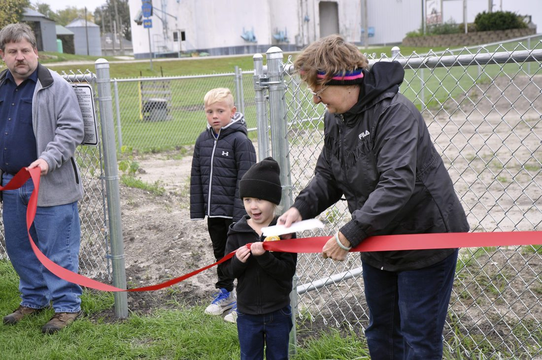 -Messenger photo by Joe Sutter  Elle Gascho, 4, is all eager to help Lori Gascho with the ribbon cutting for the new Badger BMX track this week. At left Carson Oleson and Mayor Chris Wendall look on.