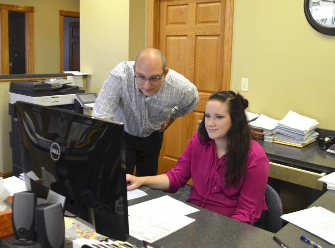 -Messenger photo by Joe Sutter  Jeremiah Schlegel, left, visits with Melissa Thompson at the Fort and Schlegel office recently. The firm has been in business for over 30 years under the name Fort and Co.