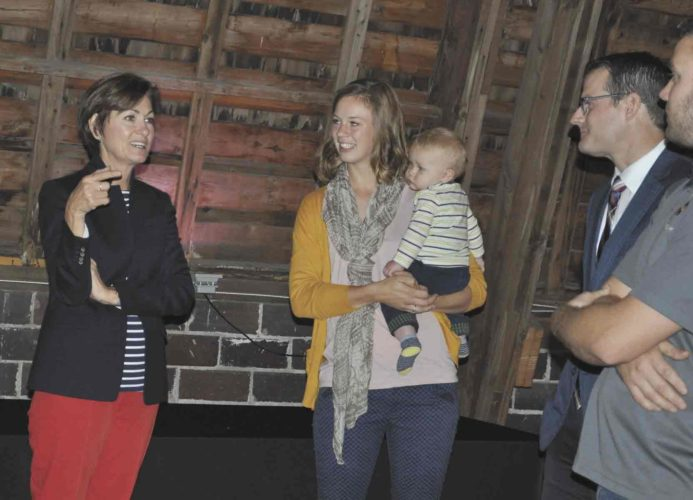 -Messenger photo by Adri Sietstra  Iowa Gov. Kim Reynolds, left, speaks with Backcountry Winery owner Amber Gable and acting Lt. Gov. Adam Gregg,  at Backcountry Winery. Reynolds visited the small business in honor of Manufacturing/Industry Day. Backcountry Winery was established in 2014 by the Gables. The winery now boasts a tasting room, production area and loft for special occasions like weddings and showers.