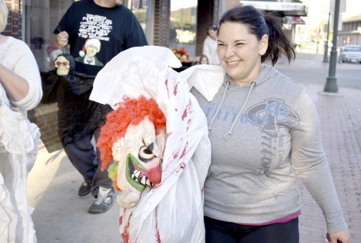 -Messenger photo by Chad Thompson  Brooke Bickford, of Fort Dodge, carries one of her clown masks down Central Avenue to the new location of the Fort Dodge Fear Factory Wednesday night.