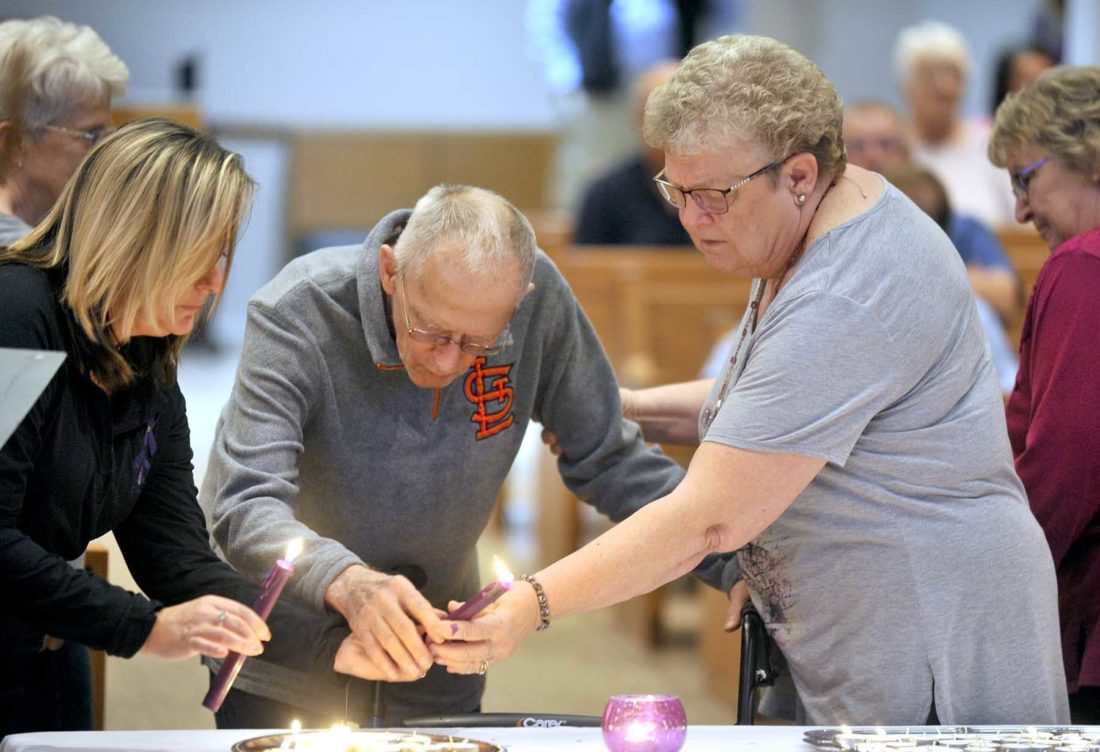 -Messenger photo by Hans MadsenLaurine and Ed Pirie, of Pocahontas, light a candle for their daughter, Gina Abens, during the 2017 Domestic/Sexual Assault Outreach Center Domestic Violence Candlelight Vigil Thursday evening at St. Paul Lutheran Church.