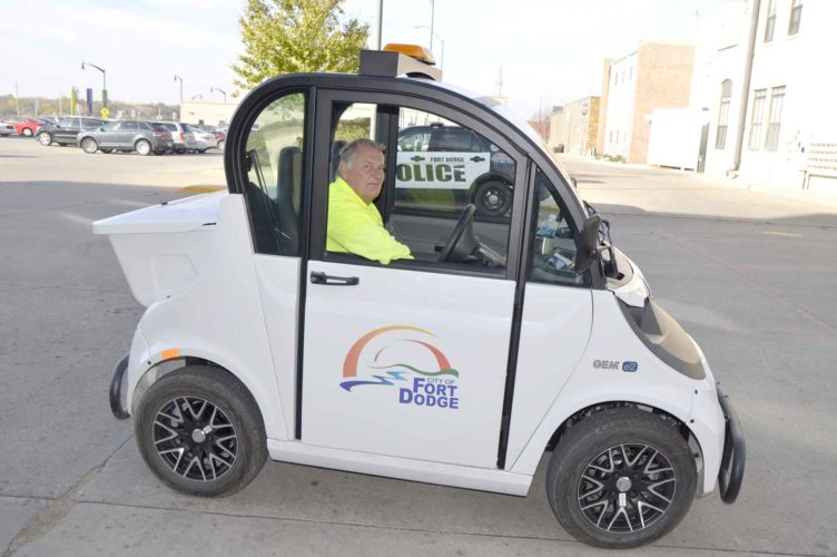-Messenger photo by Peter Kaspari  Greg Brown, a Fort Dodge parking enforcement officer, poses inside the new Polaris GEM enforcement vehicle. The new vehicle, which debuted this week, is electric and cost $9,000 less than its predecessor, which was retired due to age.