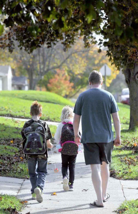 -Messenger photo by Hans Madsen  Nate Clute, right, walks his two children, Jaden Clute, 9, and Cassie Clute, 7, home from Cooper Elementary School Friday afternoon while the two children enjoy their yo-yos during the trek.