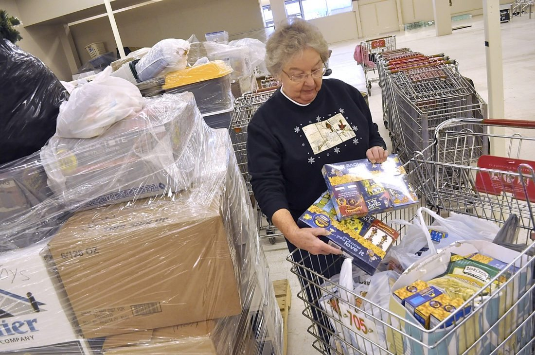 -Messenger file photo by Joe Sutter  Ruth Reed, Operation Christmas co-chair, looks through a shopping cart full of donated food in 2012, in its former location at the Crossroads Mall. Next to her are a stack of new donated items; the group hands out both new and used items.